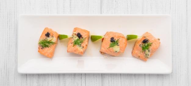 Salmone alla griglia, patate lesse e verdure su un piatto bianco