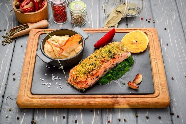 Salmone arrostito sul tagliere sulla tavola di legno