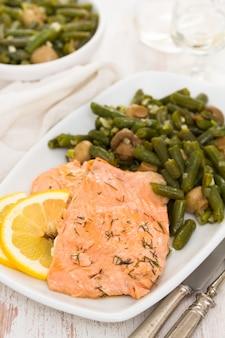 Salmone con limone e fagiolini sul piatto bianco