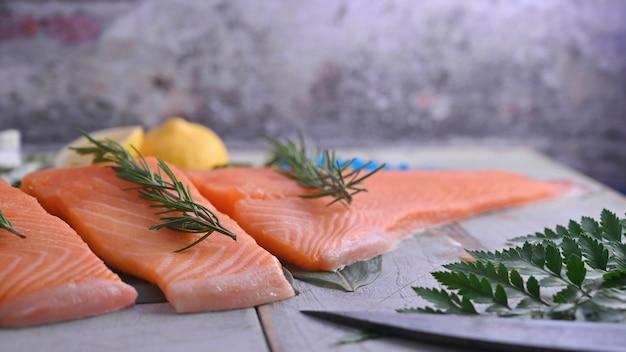 Salmone crudo e ingredienti con il coltello da cucina sulla tavola di legno.