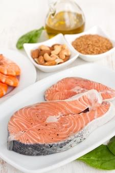 Salmone crudo, gamberetti, noci e olio d'oliva su superficie di legno