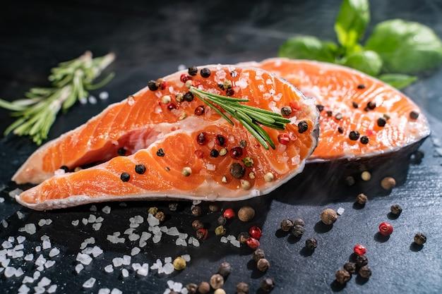 Salmone fresco con spezie e limone sul tavolo di legno