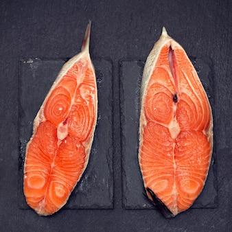 Salmone fresco crudo su superficie nera