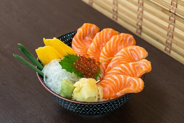 Salmone fresco sulla ciotola di riso sormontato (donburi)