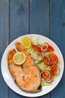 Salmone fritto con insalata di verdure e limone sul piatto su superficie di legno blu