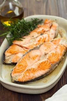Salmone fritto sul piatto su superficie di legno