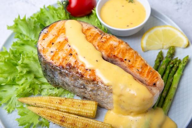 Salmone grigliato con asparagi, mini di mais e salsa olandese. avvicinamento.