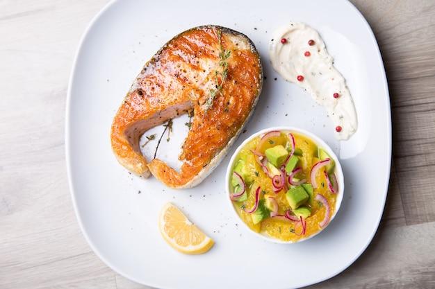 Salmone grigliato, insalata con arance e avocado. primo piano, messa a fuoco selettiva.