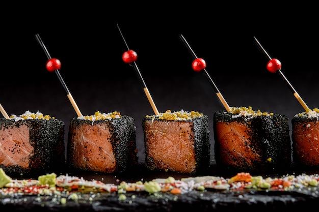 Salmone in salamoia a fette in nero impanatura, con spiedini disposti su un piatto nero. fusion food concept, low key, copia spazio.