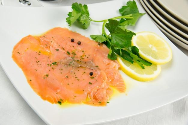 Salmone marinato con limone affettato e prezzemolo