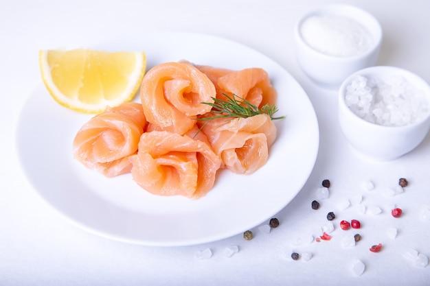Salmone salato su un piatto bianco con limone e aneto. sfondo bianco, messa a fuoco selettiva, primo piano.