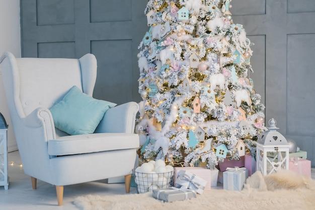 Salone alla moda della decorazione del nuovo anno con la sedia e l'albero di natale