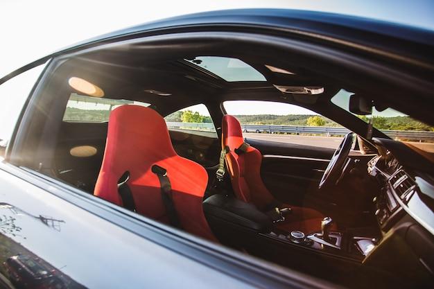 Salone interno e rosso di un'auto di berlina di lusso nera.