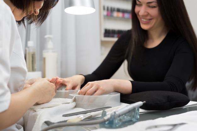 Salone per le unghie. primo piano della mano femminile con i chiodi naturali sani che ottengono procedura di cura dell'unghia. mani che rimuovono le cuticole con lo strumento professionale del chiodo, tagliatore di metallo. manicure di bellezza