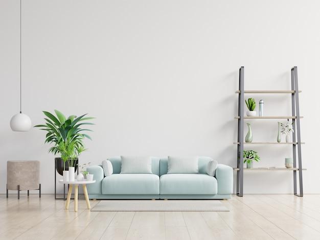 Salone vuoto con il sofà, le piante e la tavola blu sul fondo bianco vuoto della parete.