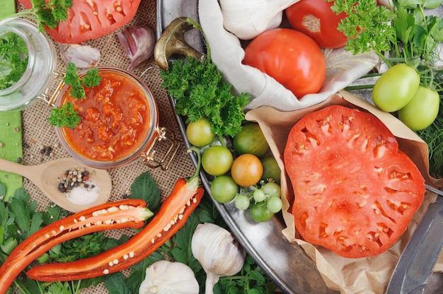 Salsa al pomodoro ed ingredienti per la sua cottura sul piatto di metallo. vista dall'alto.