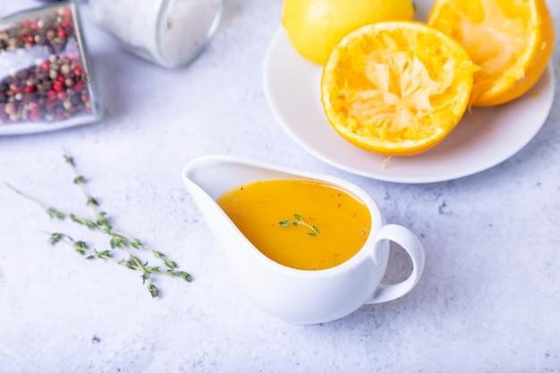 Salsa all'arancia per anatra (pollame) in una salsiera bianca. primo piano, messa a fuoco selettiva.