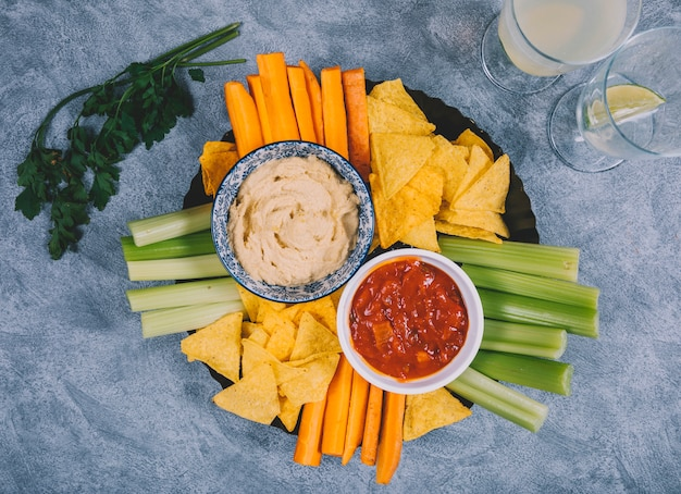 Salsa di guacamole e salsa in una ciotola con carota; gambo di sedano; succo; chip di coriandolo e tortilla su sfondo concreto