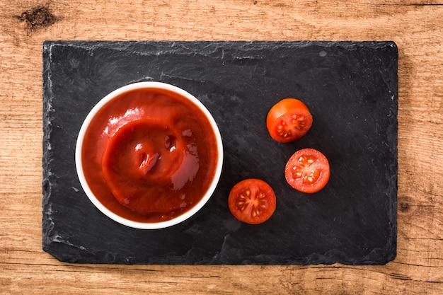 Salsa di ketchup in ciotola e pomodori sulla vista di legno del piano d'appoggio