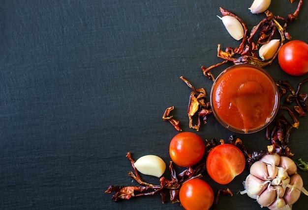 Salsa di pomodoro con aglio e pepe secco su ardesia scura, vista dall'alto