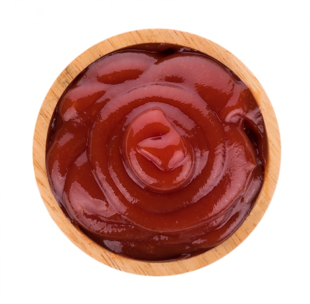 Salsa di pomodoro in ciotola di legno isolata
