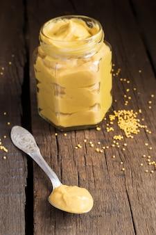 Salsa di senape fatta in casa in un cucchiaio e un barattolo