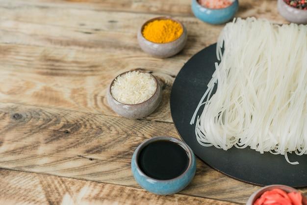 Salsa di soia; riso crudo; curcuma in ciotola vicino a spaghetti di riso essiccati sul vassoio nero su sfondo texture di legno
