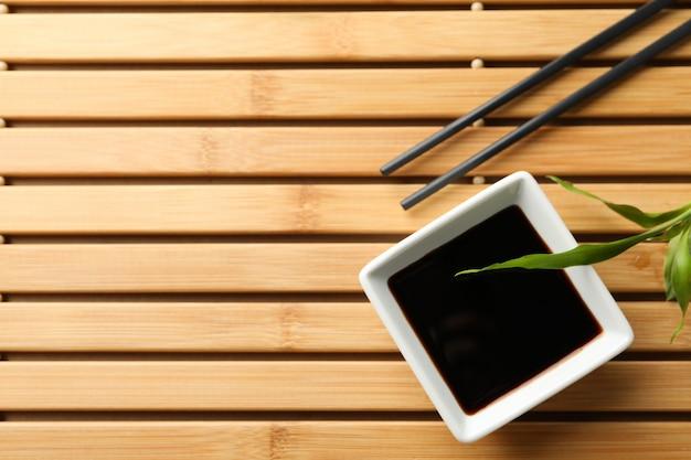 Salsa di soia su fondo di legno, spazio per testo. vista dall'alto