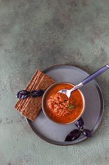 Salsa di verdure fatta in casa con basilico viola in una ciotola di ceramica e cracker multicereali.