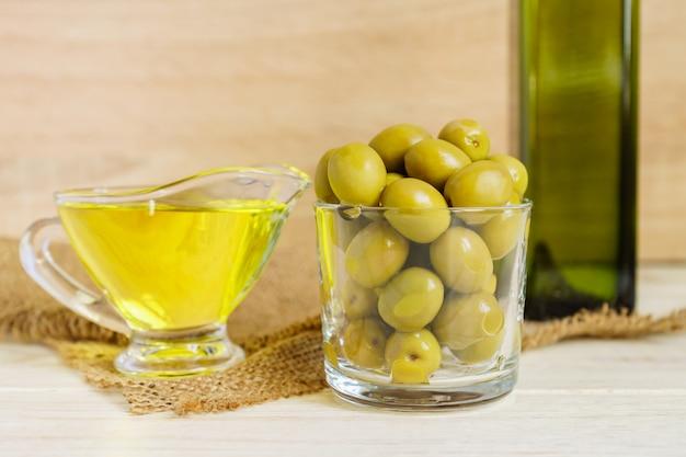 Salsa di vetro con olio extra vergine di oliva e vaso di olive verdi marinate su tela da imballaggio sul tavolo di legno.