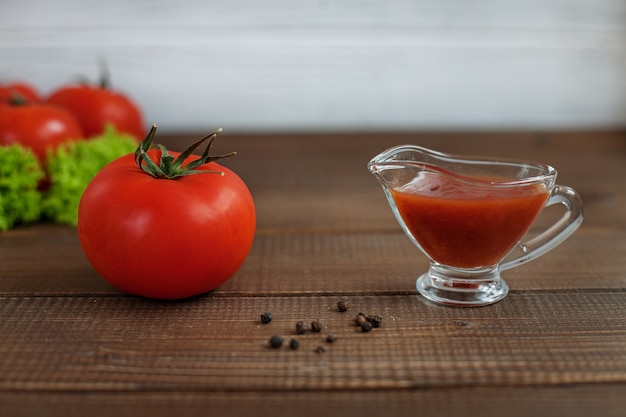 Salsa, lattuga e pomodoro su un tavolo di legno. il concetto di mangiare sano e vegetarismo.