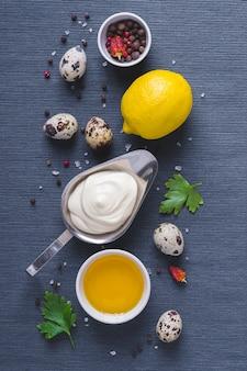 Salsa maionese ed ingredienti sul fondo blu del panno