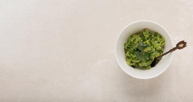Salsa messicana del guacamole in una ciotola bianca su un fondo concreto, cima, spazio della copia
