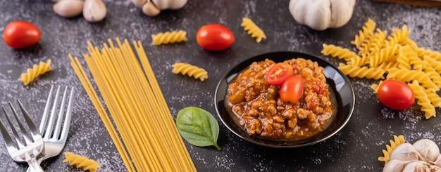 Salsa per saltare in padella spaghetti o maccheroni saltati in padella su un piatto nero.