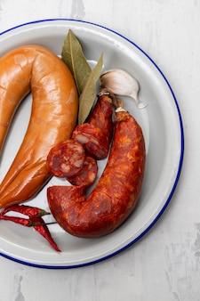 Salsicce affumicate sul piatto con peperoni