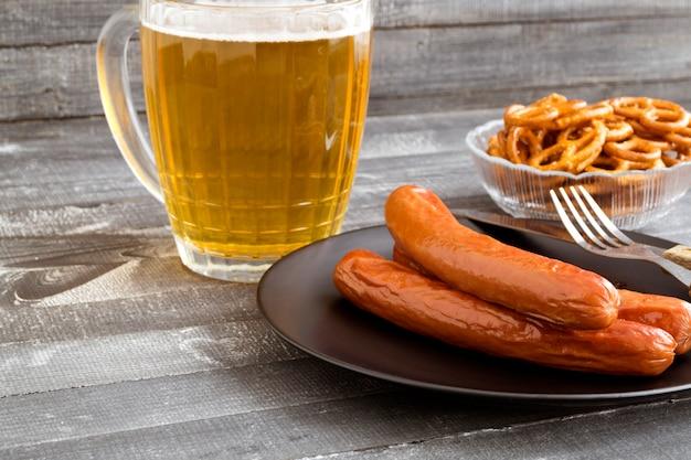 Salsicce alla griglia con birra su un tavolo di legno.