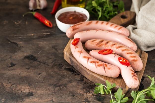 Salsicce alla griglia con ketchup, erbe e peperoncini
