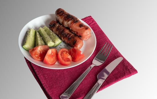 Salsicce alla griglia con pomodori e cetrioli