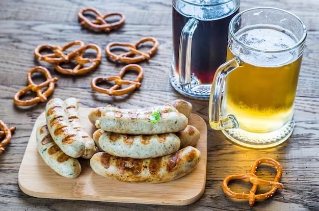 Salsicce alla griglia con salatini e boccali di birra