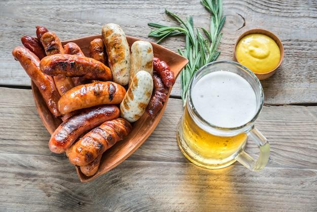 Salsicce alla griglia con un bicchiere di birra