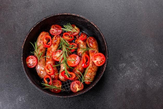 Salsicce alla griglia con verdure e spezie su sfondo nero