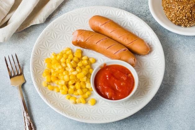 Salsicce alla griglia, mais in scatola e salsa di pomodoro su un piatto