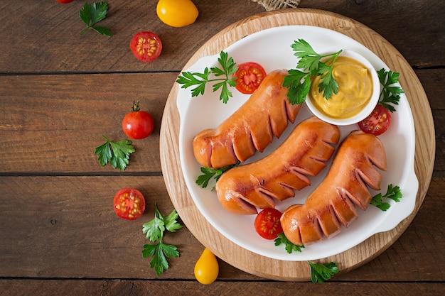 Salsicce alla griglia padella sul tavolo di legno