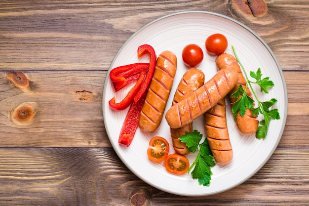 Salsicce alla griglia, pomodori freschi, peperoni e prezzemolo su un piatto su un tavolo di legno. vista dall'alto.