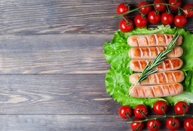 Salsicce alla griglia su foglie di lattuga verde, rosmarino, pomodorini rossi su un ramo.