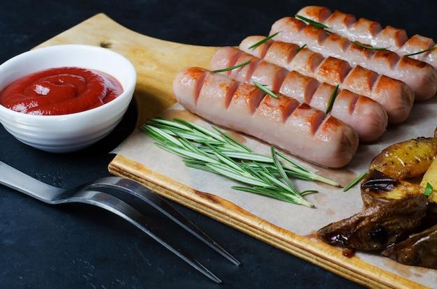 Salsicce alla griglia su un tagliere di legno. patate fritte, rosmarino, salsa ketchup. dieta malsana. sfondo scuro