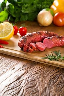 Salsicce alla griglia sulla griglia con limone, patate e pomodori