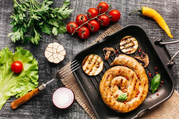 Salsicce alla lumaca alla griglia in padella con spezie e verdure su sfondo grigio in legno