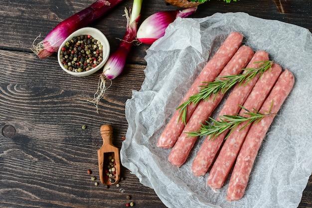 Salsicce di carne cruda per barbecue o hot dog. cipolle viola, sale e pepe, origano fresco per la marinata. cena in famiglia alla griglia