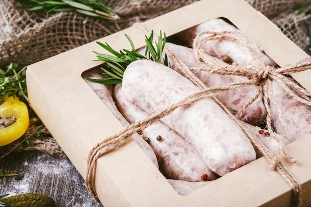 Salsicce di carne crude crude in una scatola artigianale su un tagliere rustico. spezie per carne cruda salsicce cipolle, aglio, timo, rosmarino, foglie di salvia, coriandolo, peperoni.